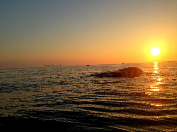 Лодка с рыбаками на закате